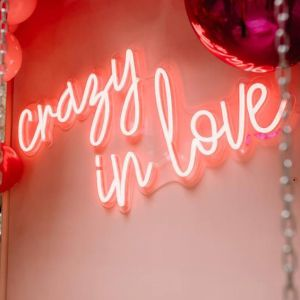 Crazy in Love LED neon light shown mounted on a wall with balloons - photo from Custom Neon by Neon Collective