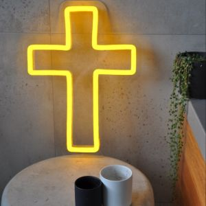 LED neon cross shown illuminated in yellow, on a side table - from Custom Neon by Neon Collective