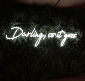 Darling, so it goes Neon Sign Quote for Weddings & Home Decor shown on green wall  - photo from Custom Neon by Neon Collective