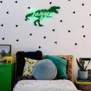 Personalised LED neon child's name sign with dinosaur background shown in child's bedroom- from Custom Neon by Neon Collective