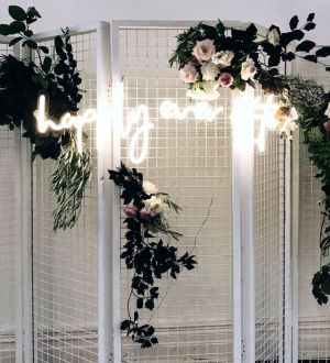 Happily Ever After Neon Sign shown with wedding flowers on a mesh screen - photo from Custom Neon by Neon Collective