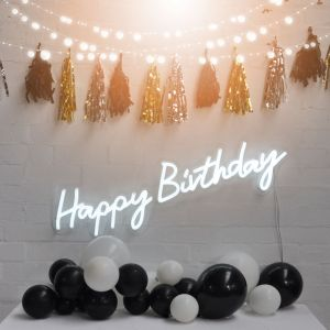 Happy Birthday illuminated sign from Custom Neon, shown on brick wall with party decorations. - photo from Custom Neon by Neon Collective