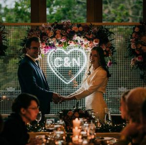 Beautiful LED neon heart light personalised with the bride & groom's initials. Shown here on a mesh background surrounded by a floral arrangement. Photo from Custom Neon by Neon Collective