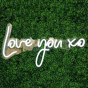 Love You XO LED Neon Light Sign for Weddings shown on green wall background