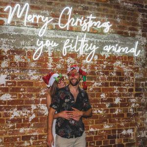 Merry Christmas You Filthy Animal LED Neon Sign shown on an exposed brick wall at a Xmas party - photo from Custom Neon by Neon Collective