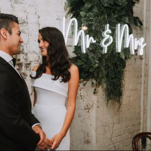Mr & Mrs portable LED neon sign on clear acrylic backboard. Shown on exposed brick wall. - Photo Custom Neon by Neon Collective